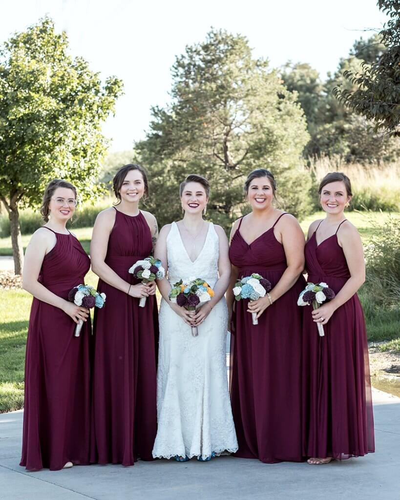 Bride in a white gown, and 4 bridesmaids in burgundy floor length gowns, holding their bouquets.