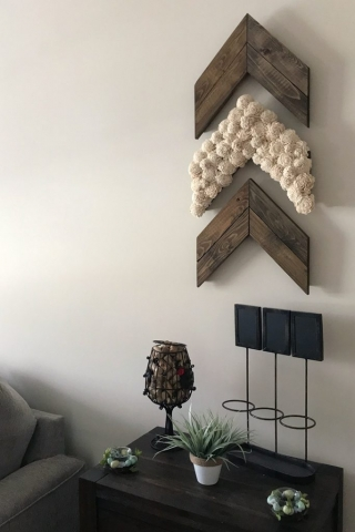 Three stained wooden chevron arrows hung vertically on a living room wall. One arrow is covered with ivory sola flowers.