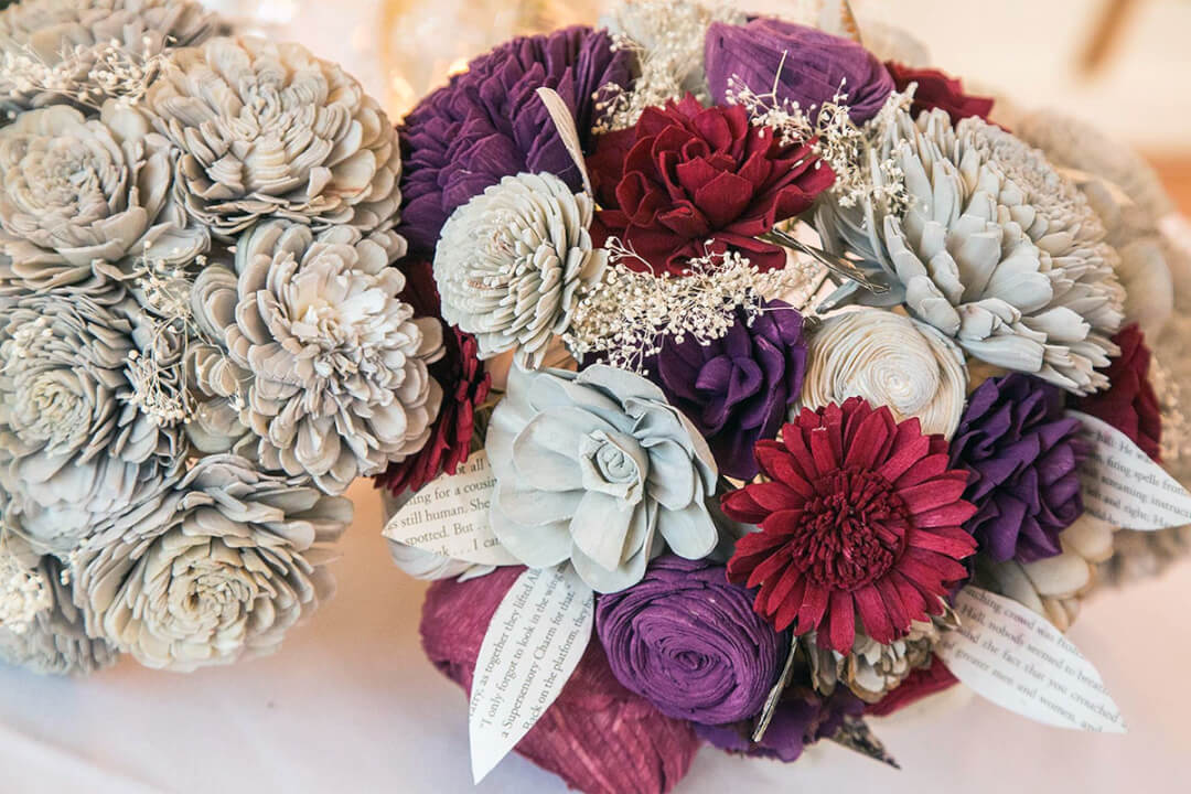 Close up of gray, purple, and red wood flower bouquets.