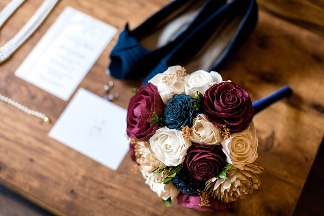 Burgundy, navy, and ivory wood flower bridal bouquet placed on a dark wood table with the bride's navy shoes and accessories.
