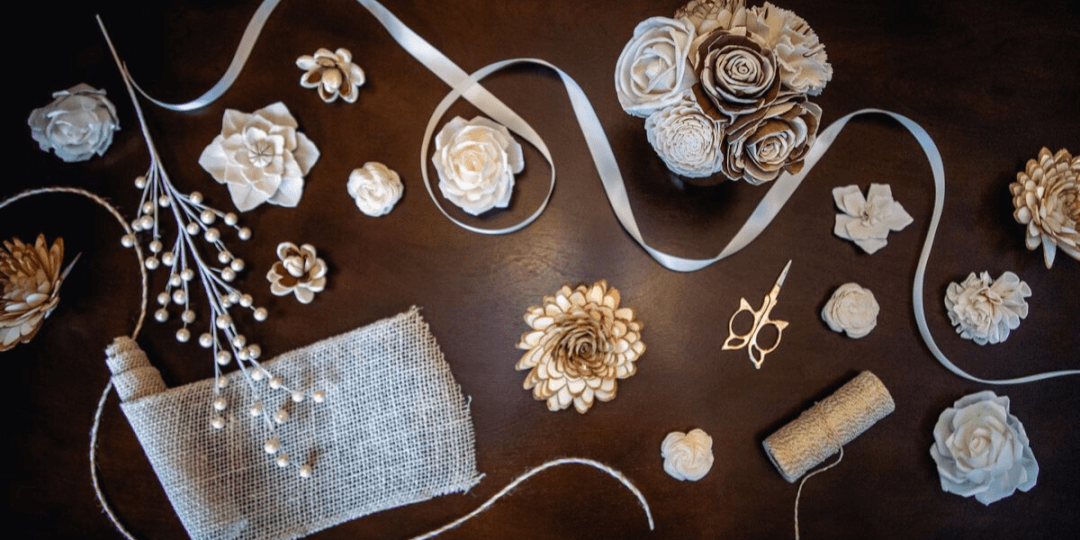 White and gold flowers and craft supplies arranged on a dark wood background