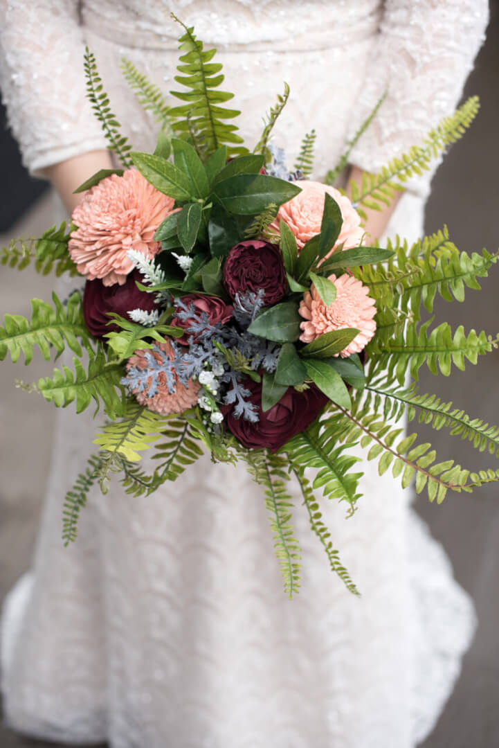 Wild boho bridal bouquet of burgundy and blush pink sola flowers, ferns, and other greenery. Photography by Lynn Marie.