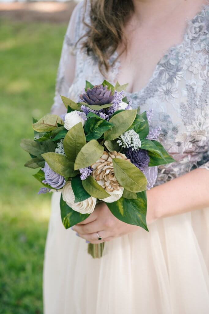 Lilac, plum, and ivory wood flower bouquet held by a bride outside in a park.