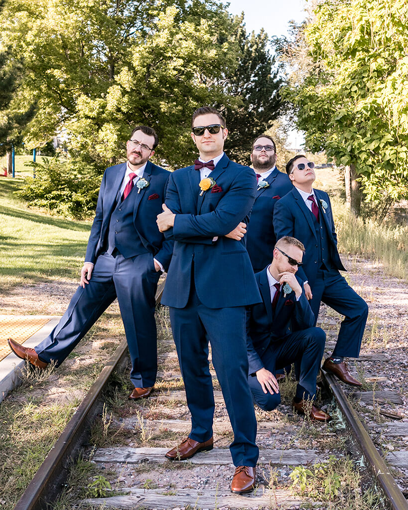 Groom and groomsmen in matching navy suits and sunglasses, posing on old railroad tracks.
