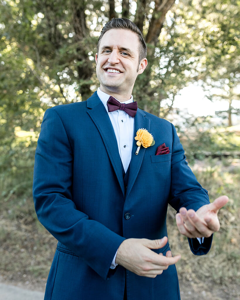 Groom in a navy suite with golden marigold boutonniere, gesturing at the camera with a big smile.