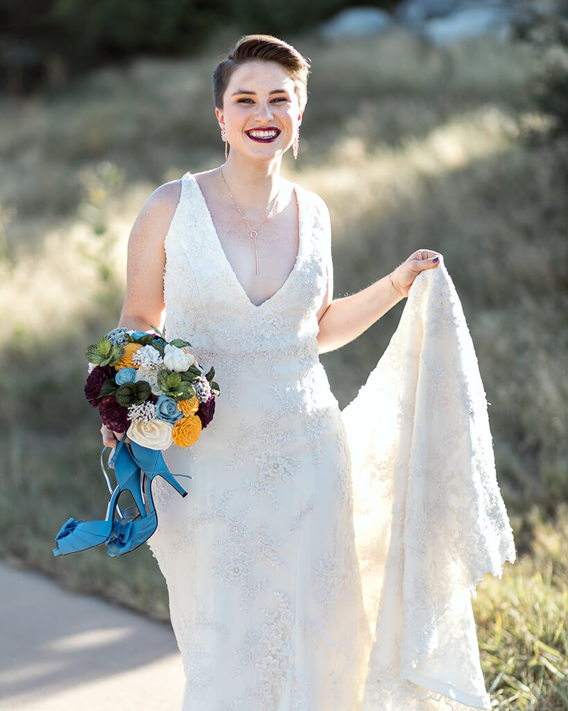 Smiling bride holding her dress up with one hand, and her bouquet and shoes in the other.