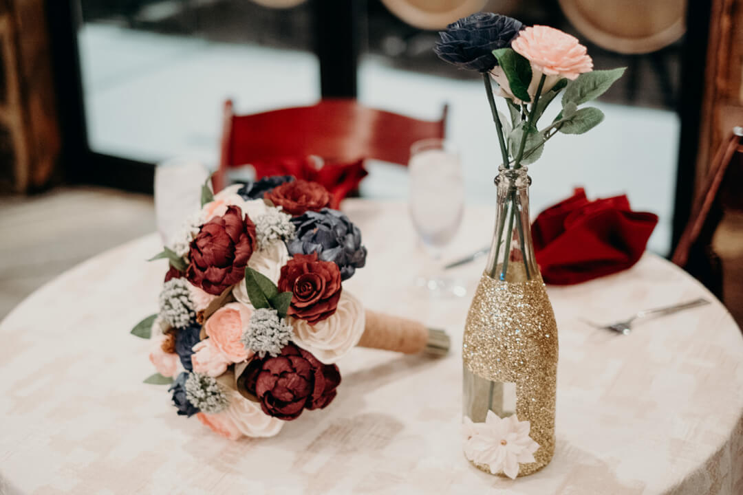 Wood flower bouquet next to glittered wine bottle centerpiece with stemmed wood flowers.