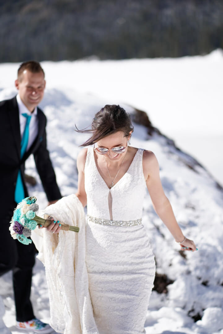 Bride in sunglasses and white dress, hiking on a snowy mountain, holding a white, blue, and purple bouquet.
