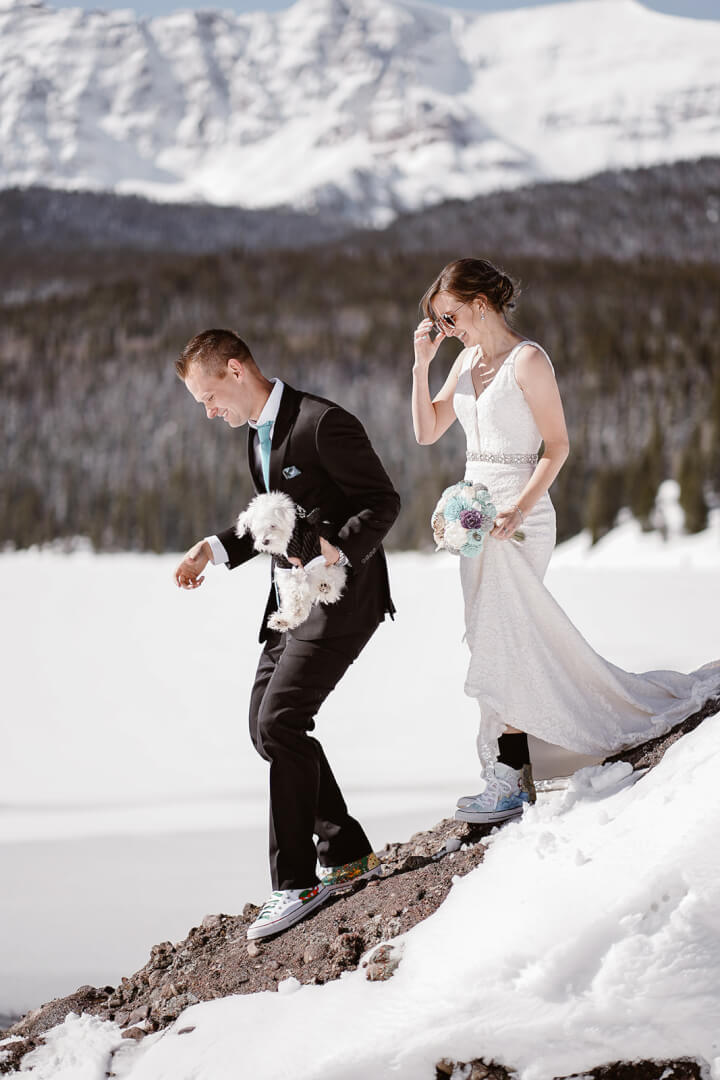 Smiling bride and groom hiking on a snowy mountain. The bride is holding her dress up with one hand, the groom is carrying their small, white dog.