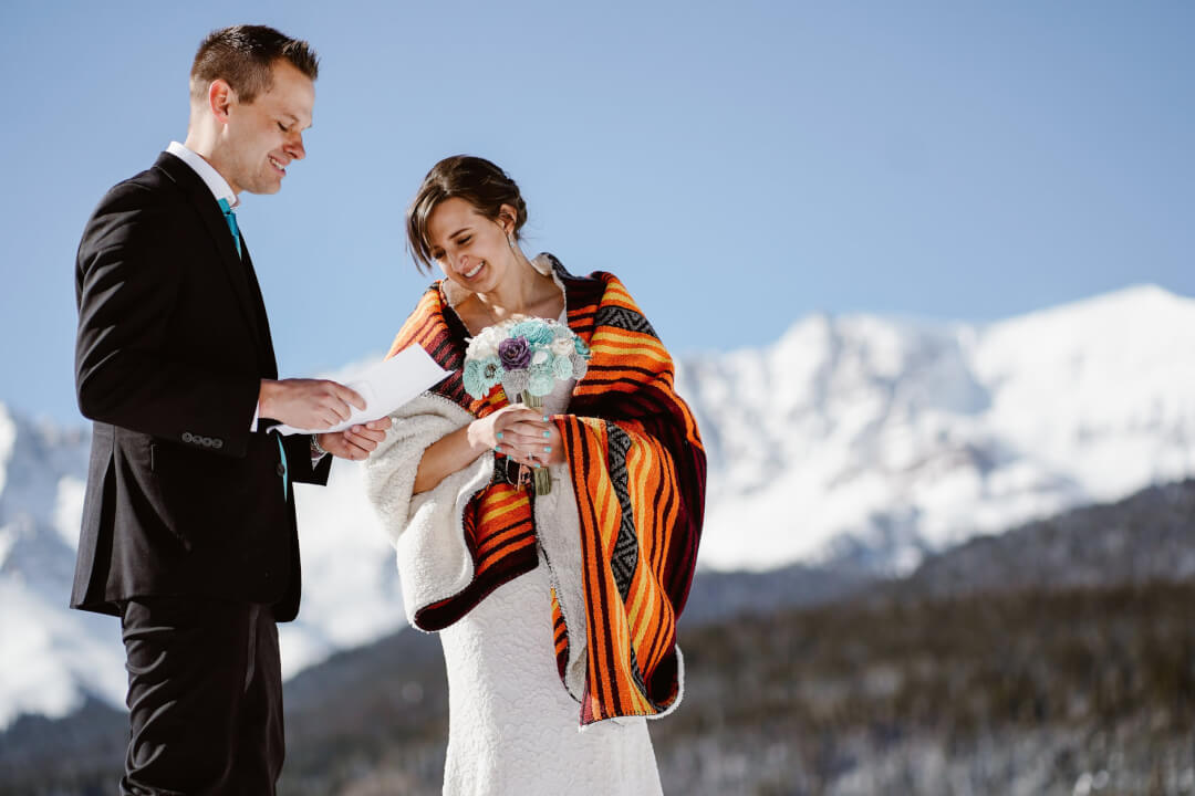 Groom reciting vows to bride wrapped in a bright orange shawl, atop a snow-covered mountain.