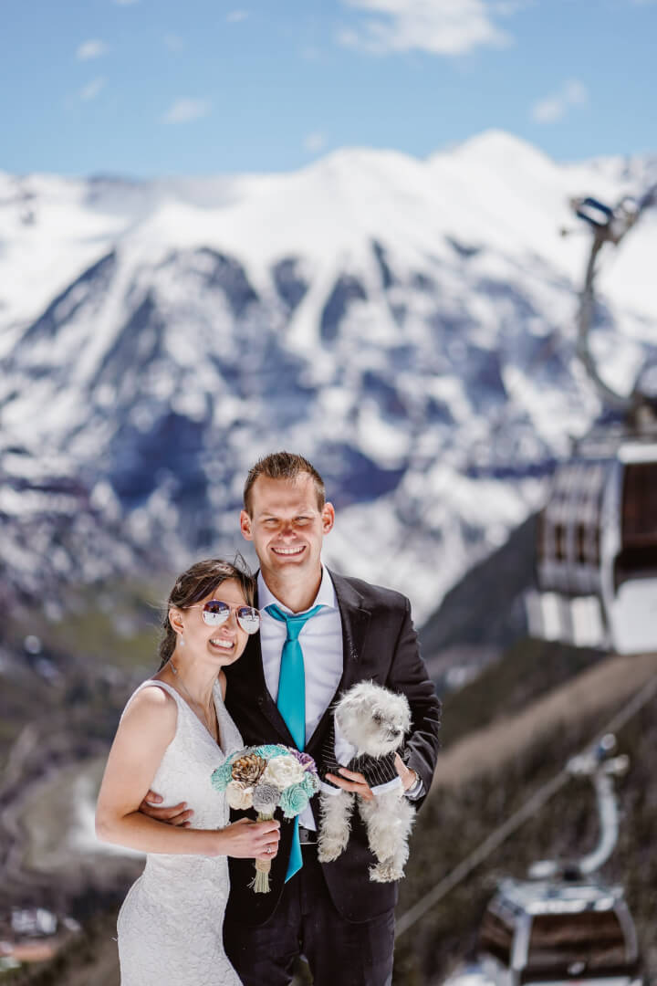 Bride and groom at the top of a ski lift, holding their dog and flowers.