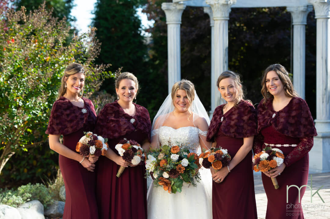 Outdoor portrait of a bride and 4 bridesmaids, with columns in the background, at The Waterfall in Wilmington, Delaware.