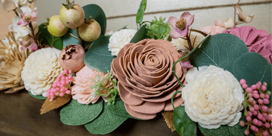 Ivory, blush, and rose gold flower arrangement with eucalyptus and berries accents.