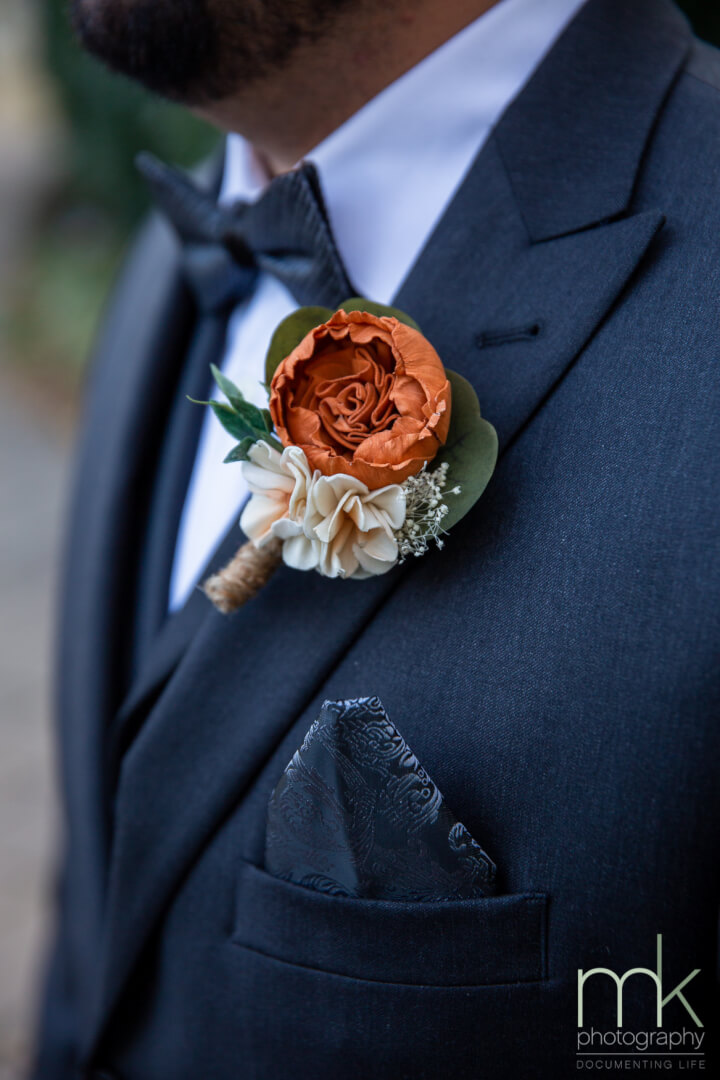Groom's boutonniere with a orange garden rose and ivory  hydrangeas.