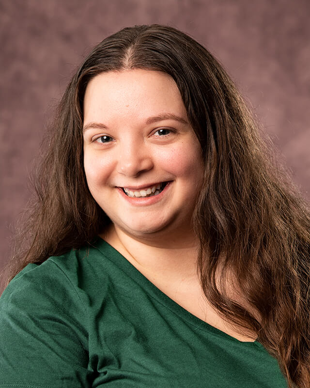Portrait of Katie: a young woman with long brown, curly hair wearing a green tshirt.